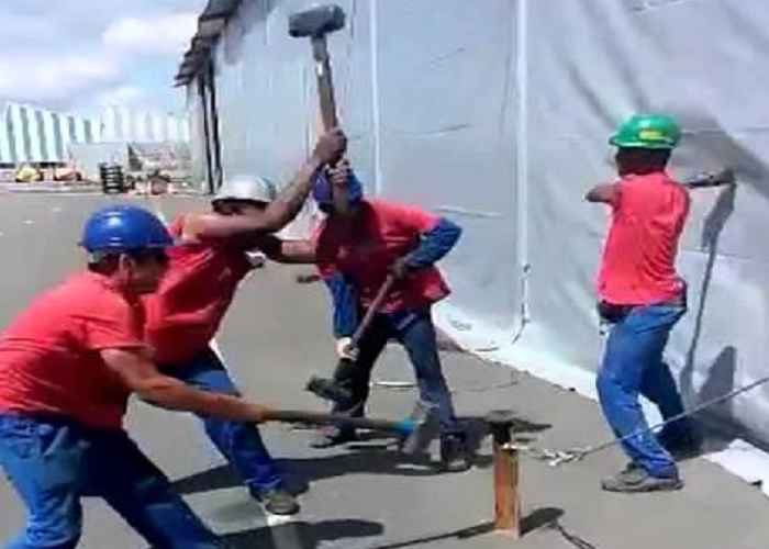 A Group Of Workers Hammer A Tent Peg In Perfect Harmony